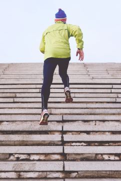 man in winter workout clothes running up stairs