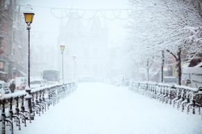 a wintery town street with street lamps