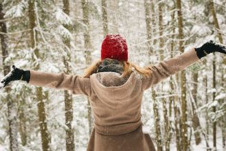 girl standing in the snow with gloves, tan coat and red hat on