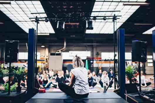 yoga teacher demoing exercise to class