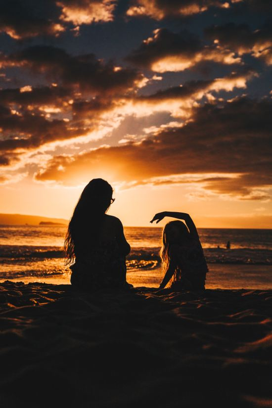 mother and daughter on the beach at sunset