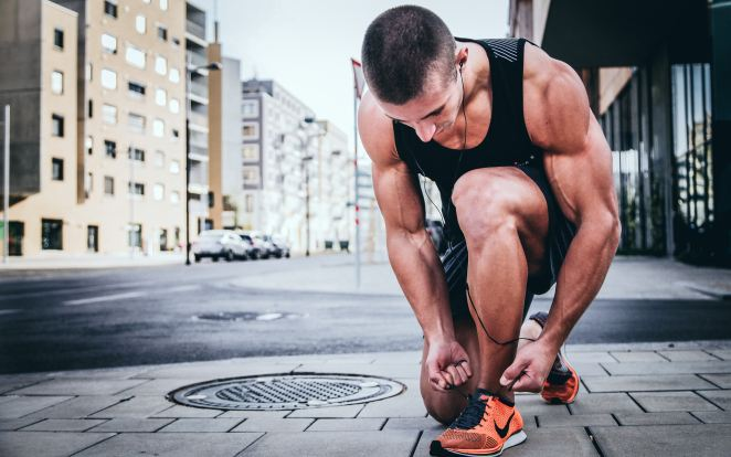 muscular man kneeling down to tie running shoes with earbuds on