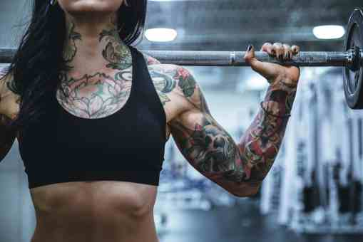 girl with tattoos working out with barbell on back