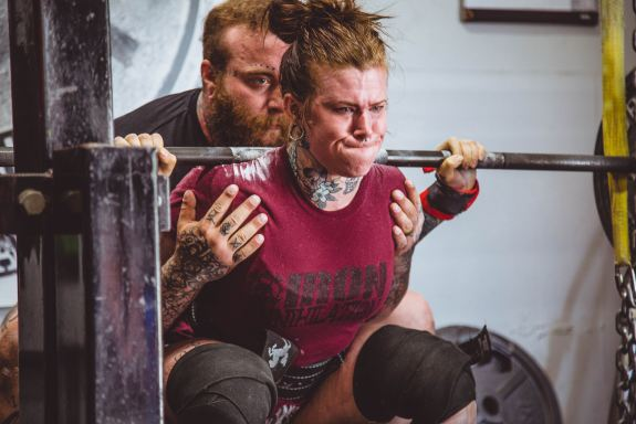 female lifting heave weight with a barbell with a male spotter