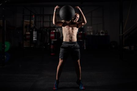 man carrying heavy stability ball on shoulder