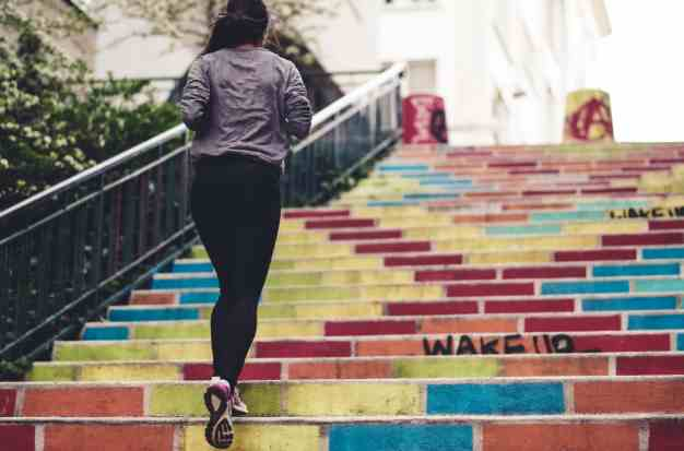 women running up colorful stairs
