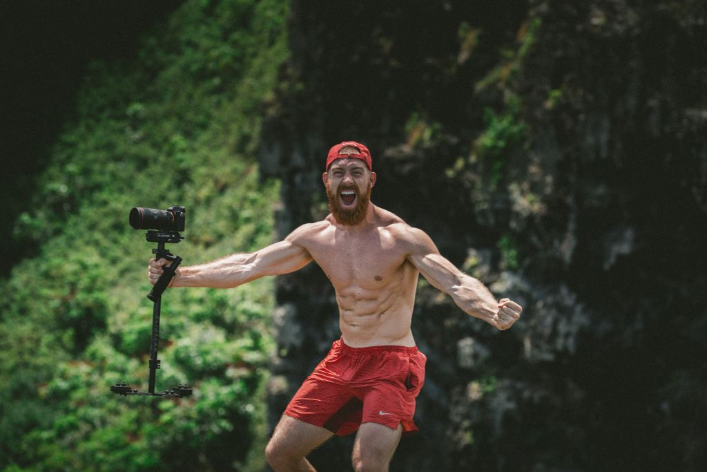 man without shirt six pack abs holding camera