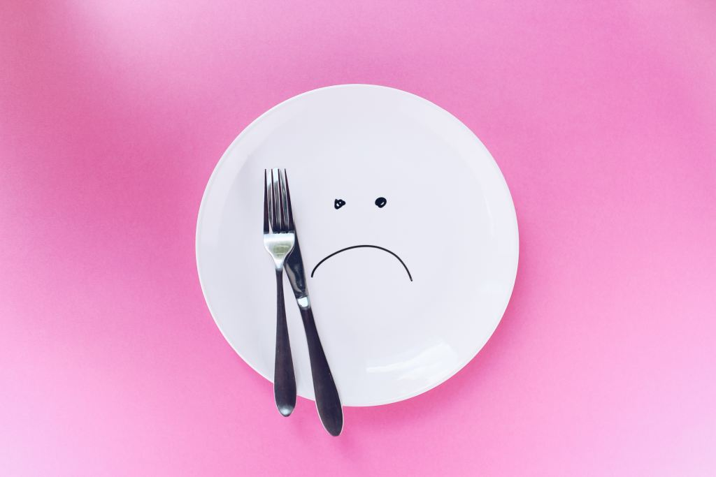 plate with a sad face and fork and knife
