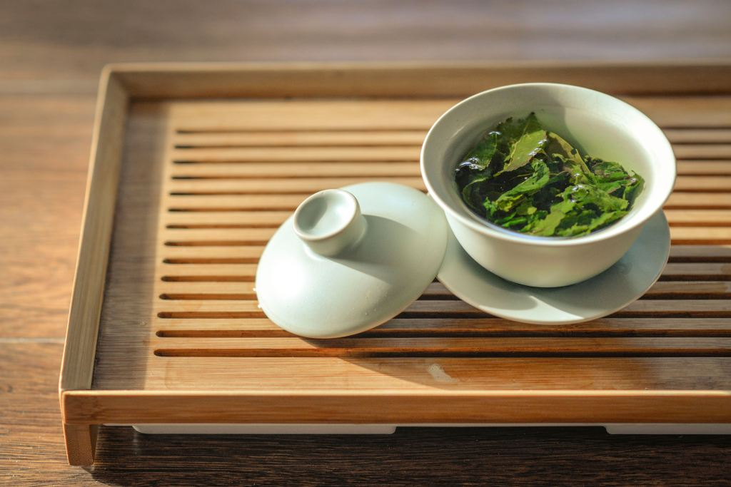 green tea leaves in white bowl on tray for energy