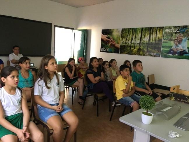 Crianças sentadas em uma classe assitem aula de Educação Ambiental