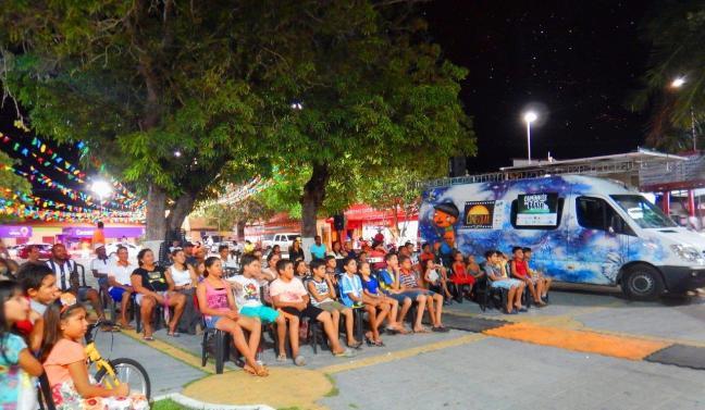 Pessoas assistem a filme a noite em uma praça