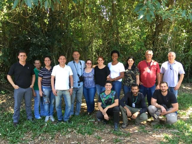 Foto mostra grupo de pessoas do Avestando, com árvores ao fundo