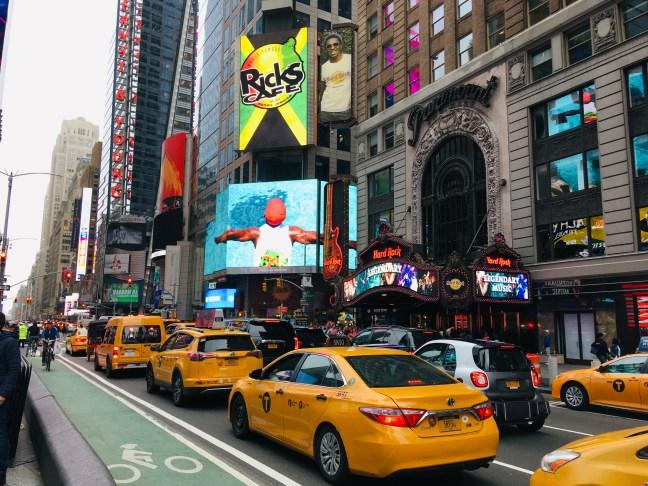 Foto mostra rua de Nova York, com táxis e ciclovia