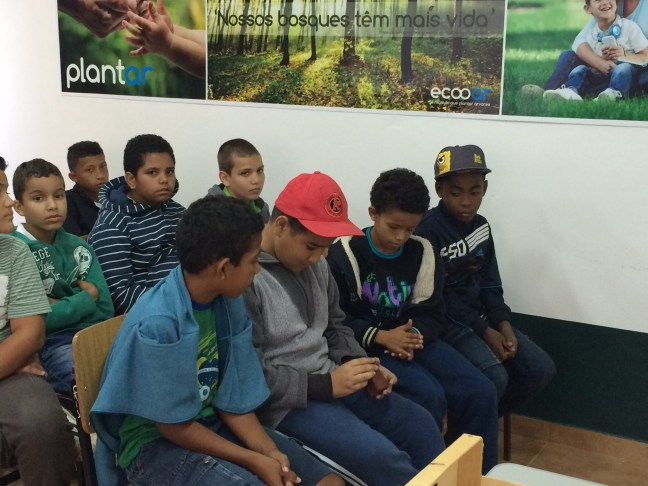 Foto mostra crianças em uma sala de aula de educação ambiental