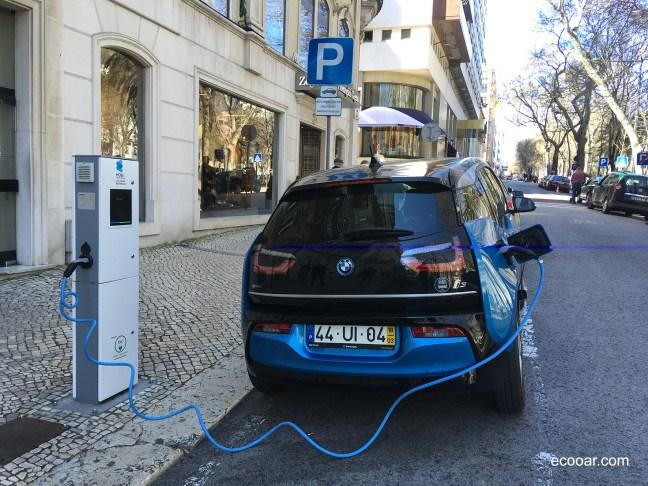 Foto mostra rua de Portugal com um carro elétrico sendo carregado