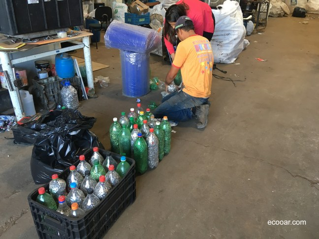 Foto mostra ação de coleta seletiva com lacres de latas de alumínio, em garrafas pet