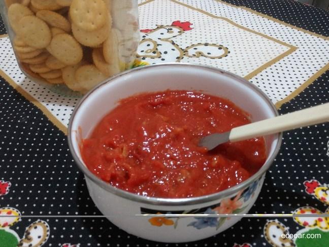 Foto mostra vasilha com geleia de goiaba sobre uma mesa, com pote de biscoitos ao fundo