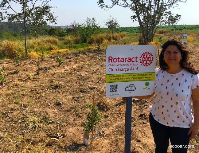 Foto mostra área de reflorestamento do Rotaract com uma pessoa próxima a placa de identificação da área