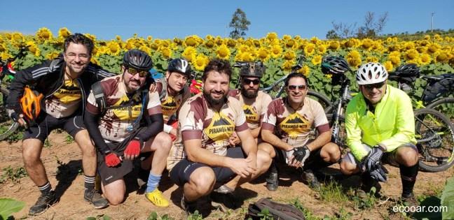 Foto mostra integrantes do Piramba MTB em frente de uma plantação de girassóis