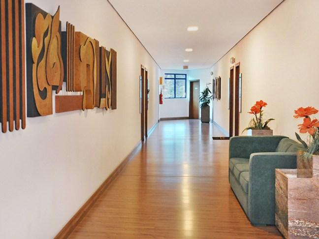 Foto mostra corredor de prédio com sofá, quadros e flores