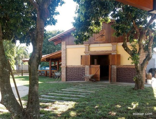 Foto mostra armazém do Recanto da Querência e duas árvores próximas