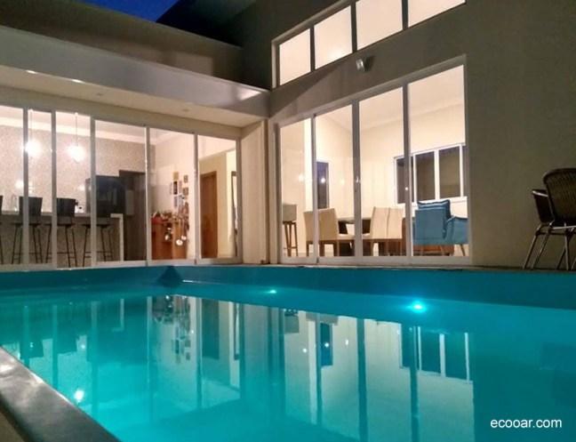 Foto mostra piscina com casa ao fundo construída da baseada na arquitetura sustentável