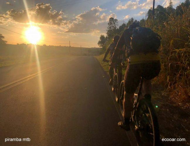Foto mostra dois ciclistas pedalando em estrada no por do Sol