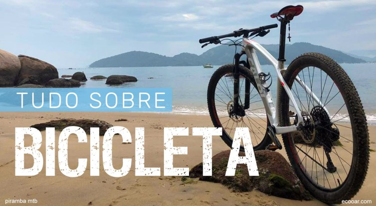 Foto mostra uma bicicleta na praia com o mar de fundo