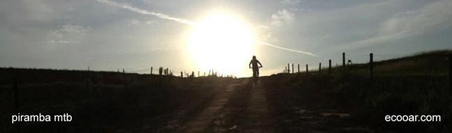 Foto mostra bicicleta no horizonte com o sol ao fundo