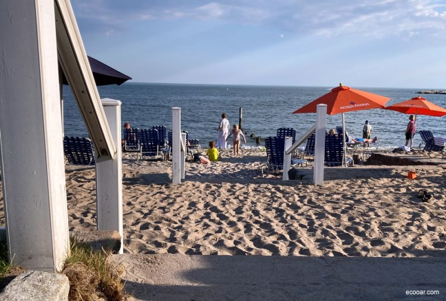 Foto mostra praia com crianças e o mar ao fundo