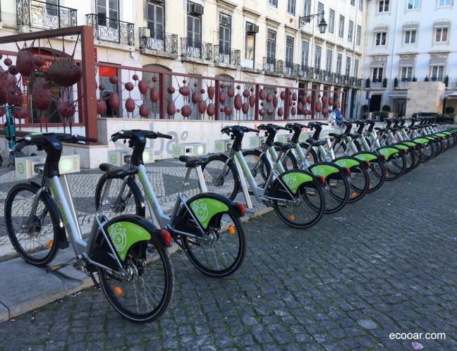 Foto mostra bicicletas para uso comum em uma praça na cidade de Lisboa, Portugal
