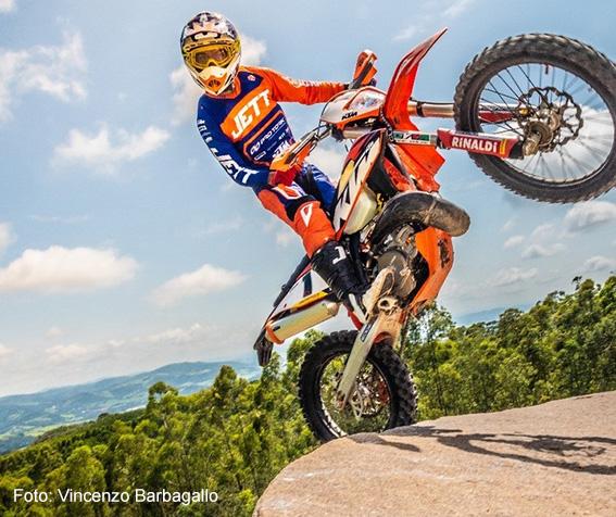 Foto mostra Rigor Rico com uma moto sobre uma pedra
