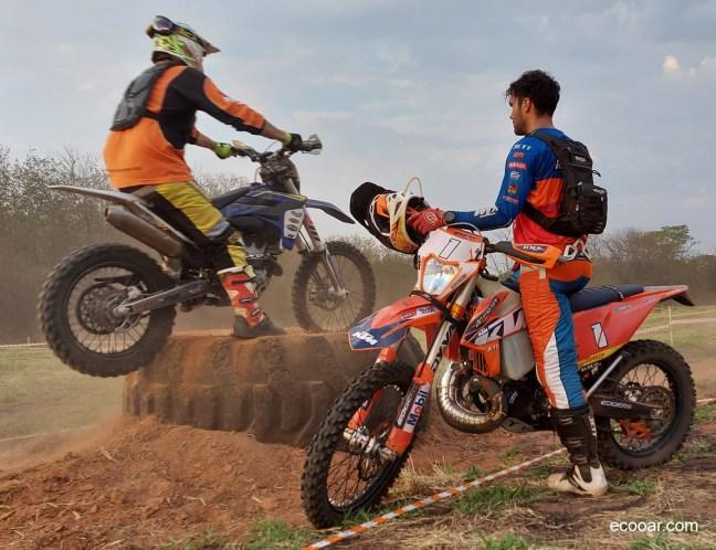 Foto mostra duas motos e Rigor Rico olhando motoqueiro fazendo manobra sobre um pneu