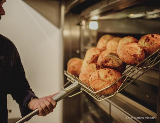Foto mostra pessoa tirando pão do forno