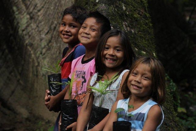 Foto mostra crianças indígenas ao pé de uma árvore, projeto que a Relax Cosméticos ajuda