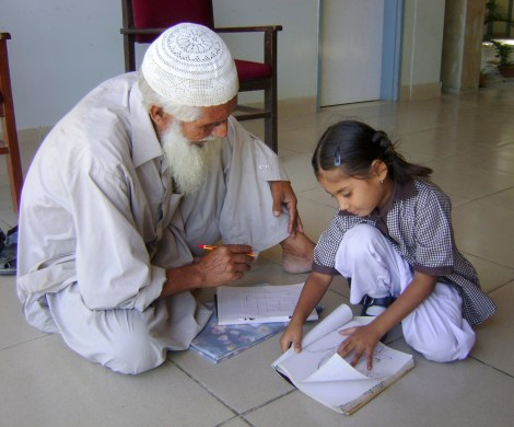 """6 Year Old Teacher, 70 Year Old Student"" - photograph taken at Korangi Academy in Karachi, Pakistan, one of Chris Baer's partner schools. Photograph by Hina Iftikhar."