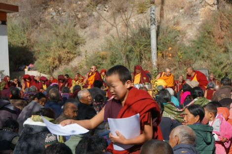 Student monk handing out Buddhist writings on nature at a community gathering.