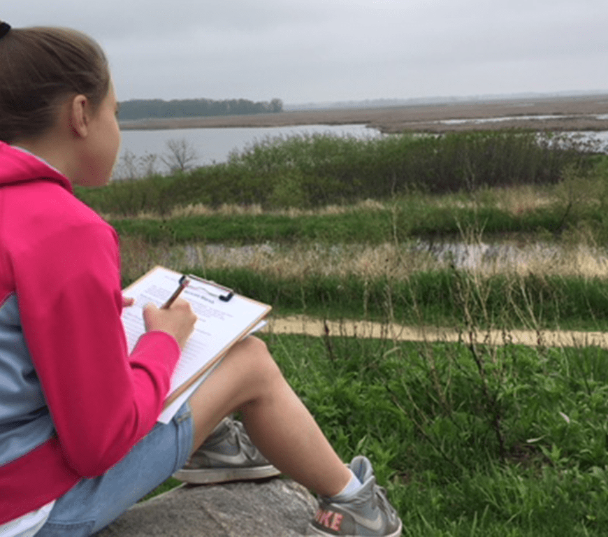 Young girl sitting with her notebook outside