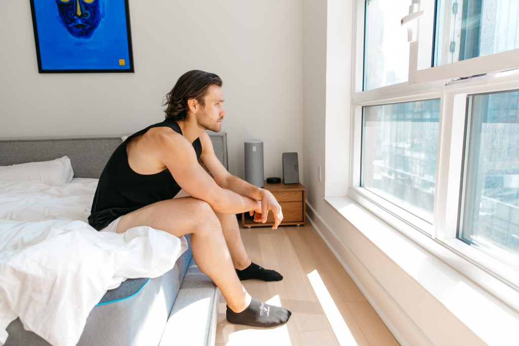 man looking out window sitting on bed