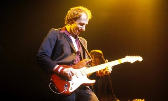 UNITED KINGDOM - JANUARY 01: Photo of DIRE STRAITS and Mark KNOPFLER; Mark Knopfler performing live onstage, playing Schecter Strat - MusicBrainz: 614e3804-7d34-41ba-857f-811bad7c2b7a, (Photo by Fin Costello/Redferns)