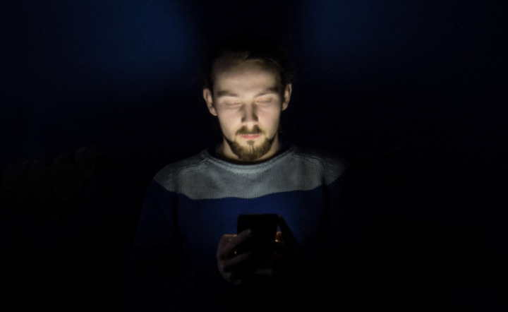 Man wearing blue shirt sitting in bed on his phone