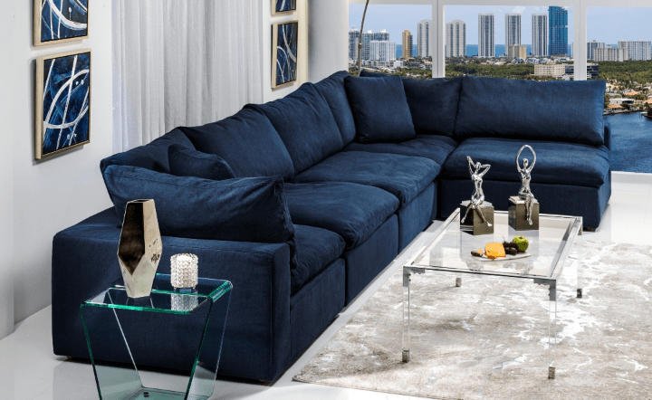Blue sofa, blue wall art, glass coffee table, glass side table, and cream rug in lifestyle setting by El Dorado Furniture