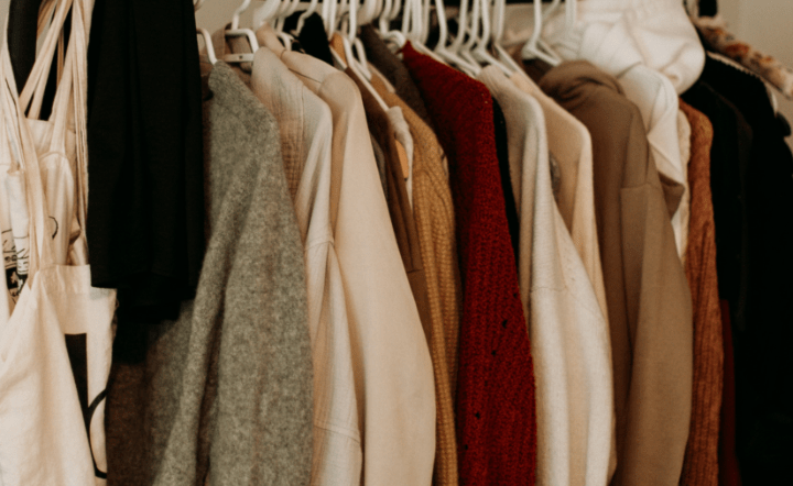 Brown, cream, and red coats on hangers in closet