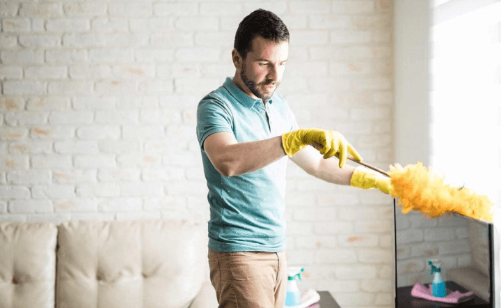 Man in aqua shirt and tan pants dusting a TV