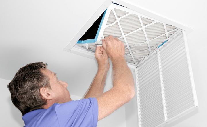 Man in purple shirt replacing air filter