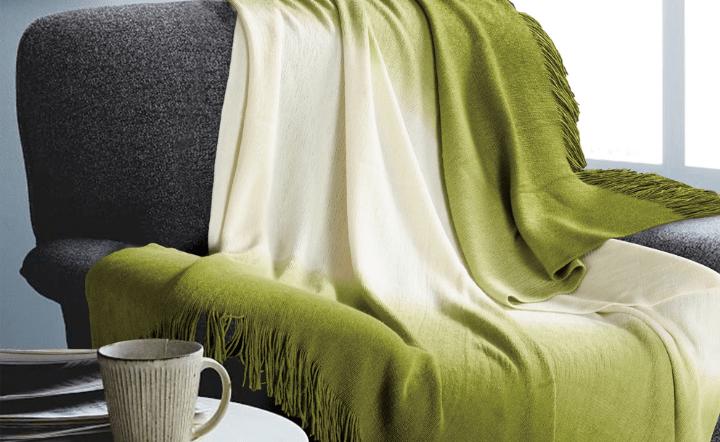 Green throw blanket on gray chair and mug on side table