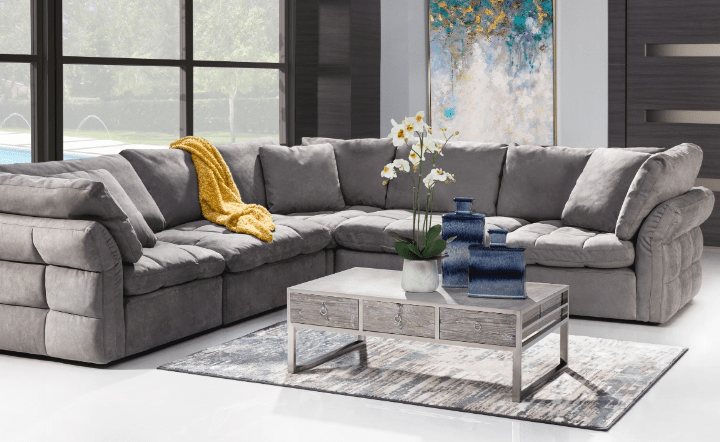 Gray sofa, plants, gray coffee table, light blue and gray rug, and blue vases in lifestyle setting by El Dorado Furniture