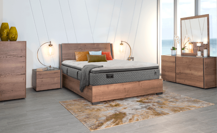 Stearns & Foster mattress on natural brown bed frame with nightstand, dresser, chest, and lamps in lifestyle setting