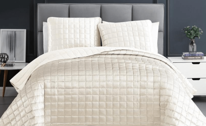 White coverlet set on gray bed with white nightstands in lifestyle setting