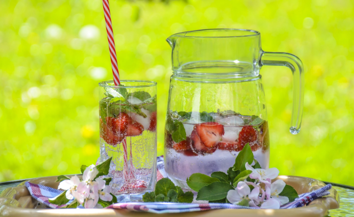 Close-up of strawberry drinks in in glass and pitcher in backyard setting